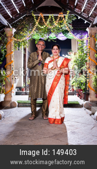 Namaste / Namaskara - Indian senior couple welcoming guests on diwali festival or wedding