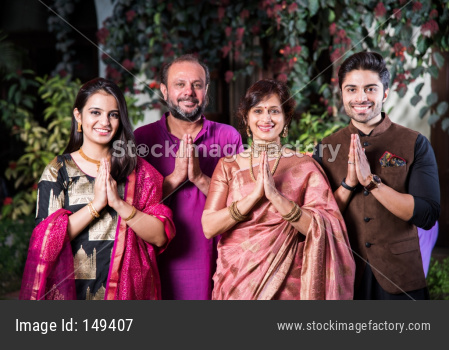 Family welcoming guests or in namaste / namaskara pose while looking at camera in celebration mood