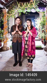 Namaste / Namaskara - Indian young couple welcoming guests on diwali festival or wedding