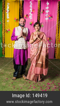 Namaste / Namaskara - Indian couple welcoming guests on diwali festival or wedding