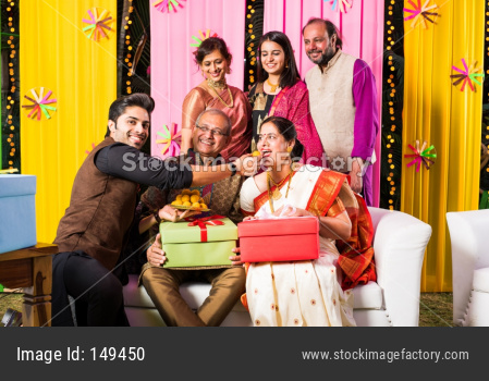 multigenerational Indian Family eating sweets while celebrating diwali festival or occasion