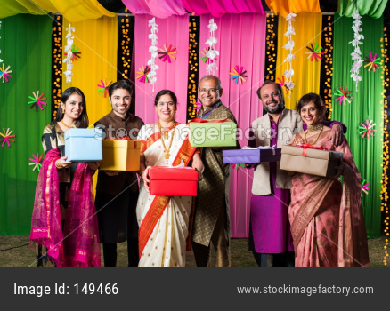 Indian family exchanging / holding Gift boxes on Diwali festival / wedding or any other ceremony. Standing against decorated bac