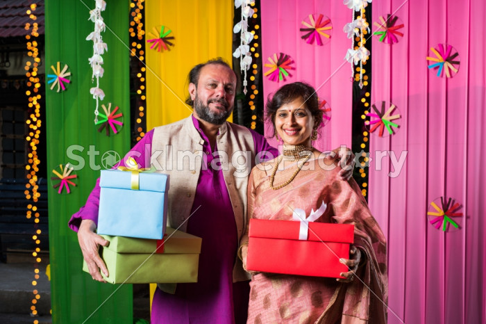 Mid Age Indian Couple Holding Diwali Gift Boxes While Standing