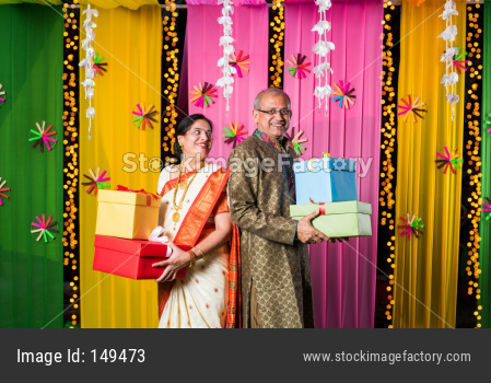 Senior Indian couple holding Diwali Gift Boxes while standing against decorative background
