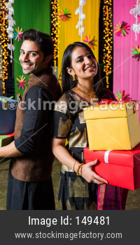 Smart Indian couple standing with gift boxes on Diwali festival or wedding ceremony