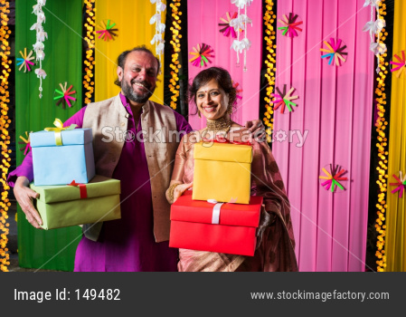 Mid age Indian couple holding Diwali Gift Boxes while standing against decorative background