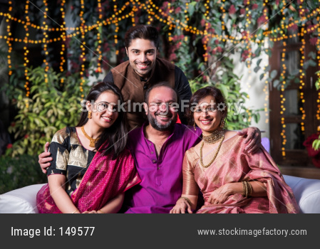 Indian Family posing for group photo on festival or wedding night, sitting on couch or round table with background decorated wit