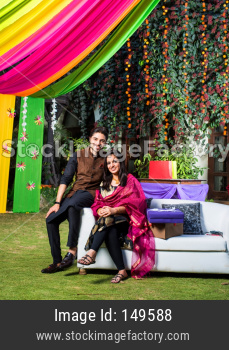 Indian young couple sitting on couch while celebrating diwali / festival or in wedding ceremony
