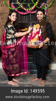 Young couple worshipping Lord Ganesha on Ganesh Festival