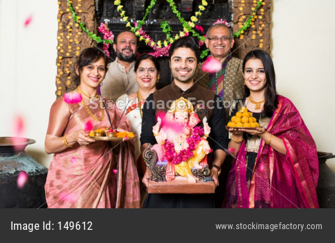 Indian family celebrating Ganesh festival with Ganesha Idol