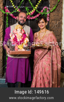 Indian couple worshipping Lord Ganesha on Ganesh Festival with Pooja Thali