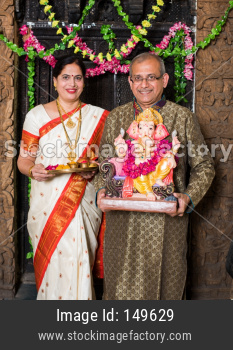 Senior Indian couple worshipping Lord Ganesha on Ganesh Festival