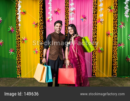 Young indian couple showing in festival shopping bags in traditional cloths with decorated background