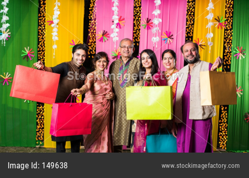 Indian family with shopping bags on Diwali festival  or wedding ceremony with decorated background