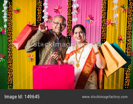 Senior Indian couple showing in festival shopping bags in traditional cloths with decorated background