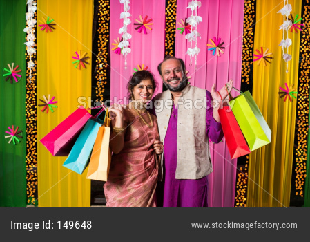 Mid age indian couple showing in festival shopping bags in traditional cloths with decorated background
