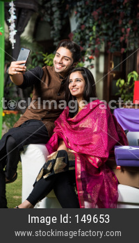 Couple taking selfie with smartphone on diwali or wedding party