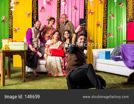 Indian family taking selfie picture using smartphone while wearing traditional festival cloths on diwali/wedding ceremony and si