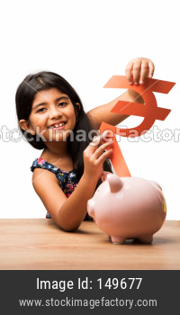 Small Girl inserting Paper Rupee symbol in piggybank