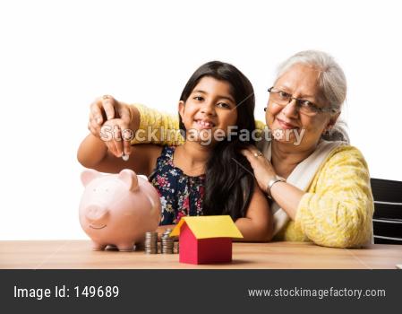 Small Girl inserting Paper Rupee symbol in piggybank