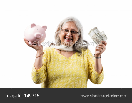 Senior woman holding money fan and piggy bank
