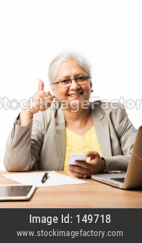 Senior woman using smartphone and laptop at office desk