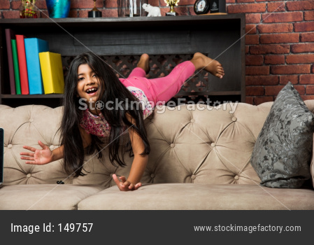 Indian/asian cute little girl jumping on sofa or couch at home
