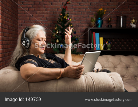senior Indian/asian women listening to music using headphones while holding a tablet computer and sitting on sofa or couch at ho