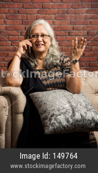 Old indian/asian lady or women using smartphone with a cup of coffee while sitting on sofa or couch at home