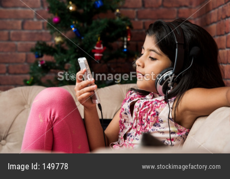 cute little indian/asian small girl listening to music using headphones or earphone on smartphone, sitting on couch or sofa at h