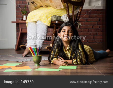 Cute little indian/asian girl colouring, drawing or painting with colours, pencils etc