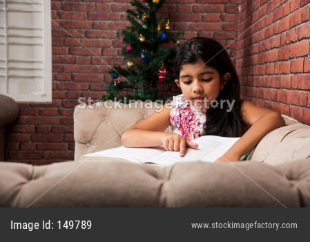 Cute little Indian/asian girl reading book while sitting sofa or couch at home
