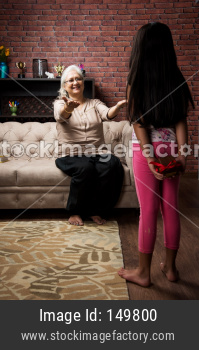 Girl giving surprise gift to  grandma