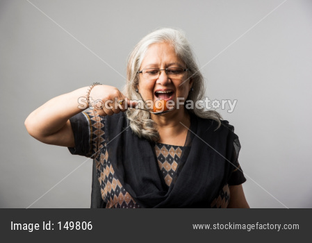 Senior Indian/asian lady eating sweet Gulab Jamun with spoon