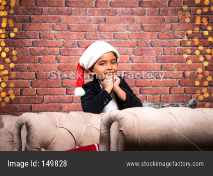 Cute little indian boy holding christmas gift and sitting on sofa on christmas evening
