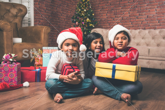 Cute Little Indian/Asian Kids Celebrating Christmas At Home With