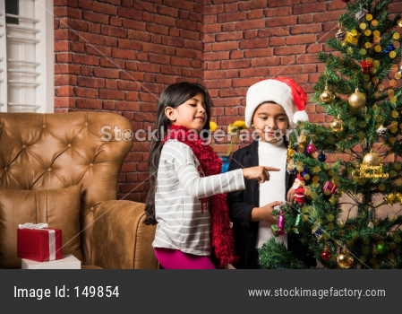 Cute little Indian/Asian kids celebrating christmas at home with Santa Hat, Gifts and Xmas Tree