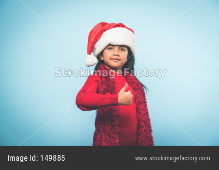 Cute little indian/asian girl celebrating Christmas while sitting in a Cardboard Box against red brick wall, indoor
