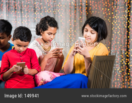 indian kids busy using smartphone in diwali - concept showing bad habbits