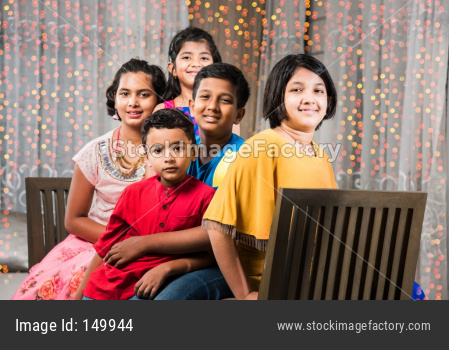 Portrait of Indian kids sitting on Sofa/Couch on diwali Festival night