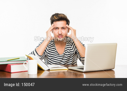 Young male college student studying on study table with books and laptop at home or classroom