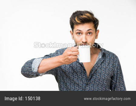 Young man having hot tea/coffee in a mug