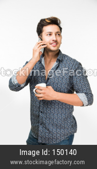 Young man having hot tea/coffee in a mug while speaking on cel phone