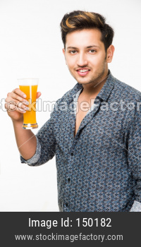Young man having cold drink or fresh juice in a glass