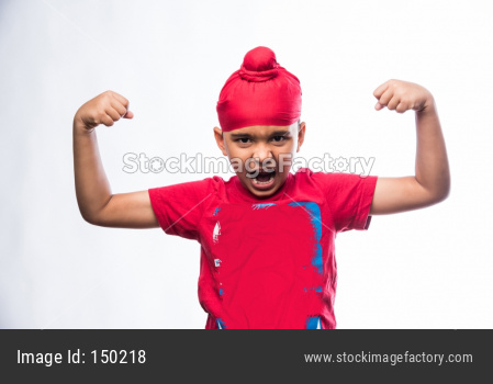 Indian sikh/punjabi little boy holding National Tricolour flag while standing isolated over white background