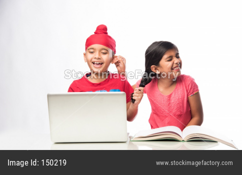 Indian Sikh/punjabi little boy studying with laptop and books at study table