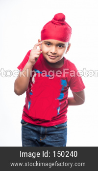 Portrait of Indian Sikh/punjabi little boy thinking while standing isolated over white background