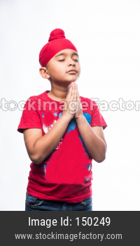 Portrait of Indian Sikh/punjabi little boy praying while standing isolated over white background