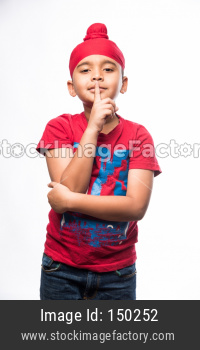 Portrait of Indian Sikh/punjabi little boy keep silence making sign while standing isolated over white background
