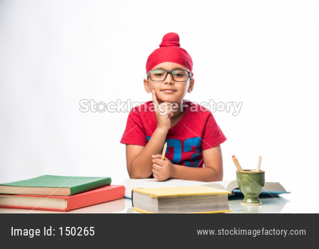 Indian Sikh/punjabi little boy studying with books at study table